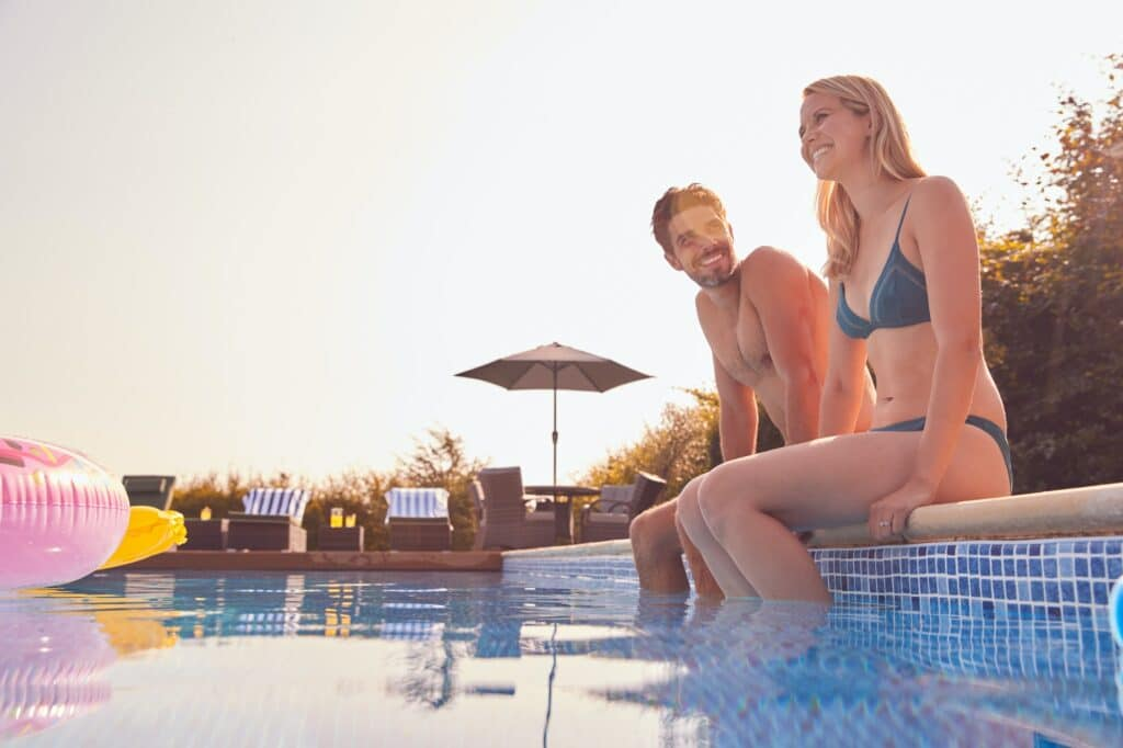 Loving Couple On Summer Vacation Sitting On Edge Of Swimming Pool